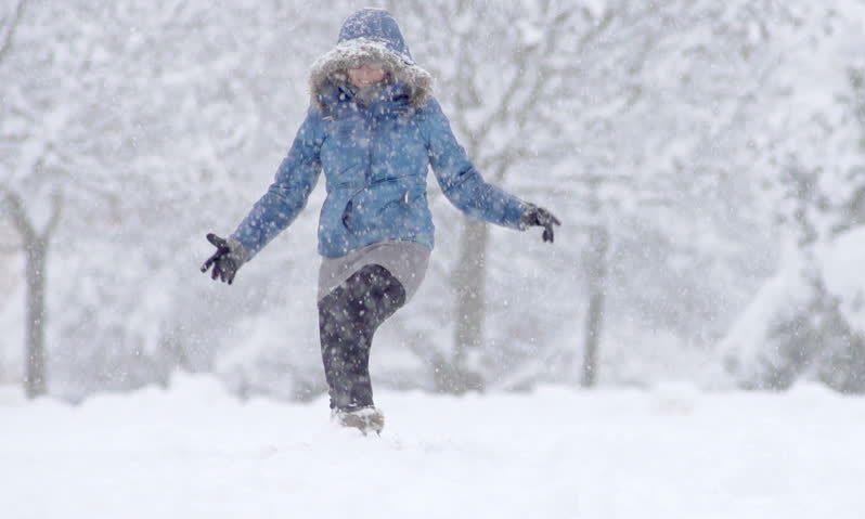 femeie care alearga prin zapada pe ninsoare